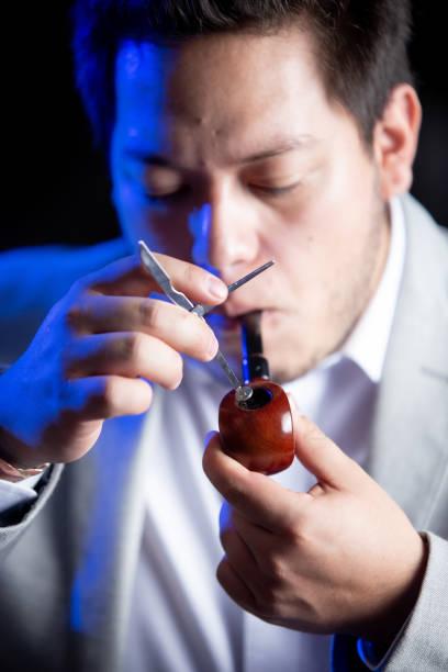 hombre de negocios preparando y fumando su pipa de tabaco - gerardo huitrón fotografías e imágenes de stock