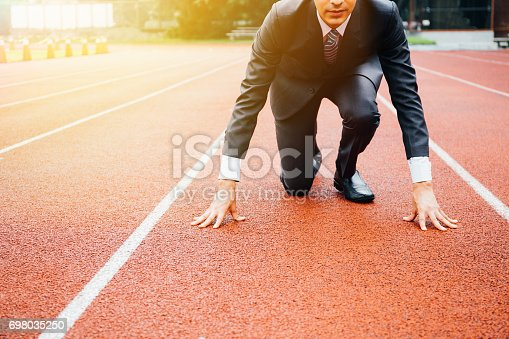 istock Business man preparing to run on the competition running track 698035250