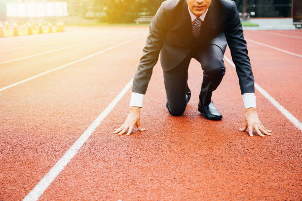 Business man preparing to run on the competition running track Business man preparing to run on the competition running track starting line stock pictures, royalty-free photos & images