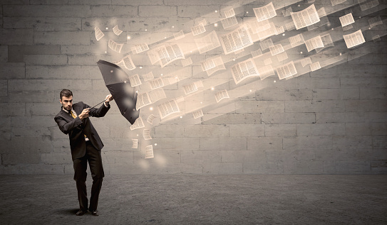 1018458132 istock photo Business man protecting with umbrella against wind of papers 1004044278