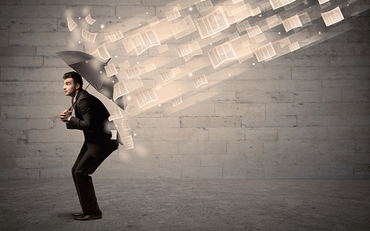 1018458132 istock photo Business man protecting with umbrella against wind of papers 1184579211