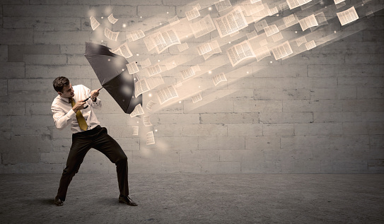 1018458132 istock photo Business man protecting with umbrella against wind of papers 940451906