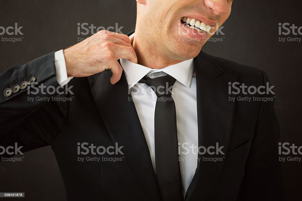 Business man pulling his shirt of his neck stock photo