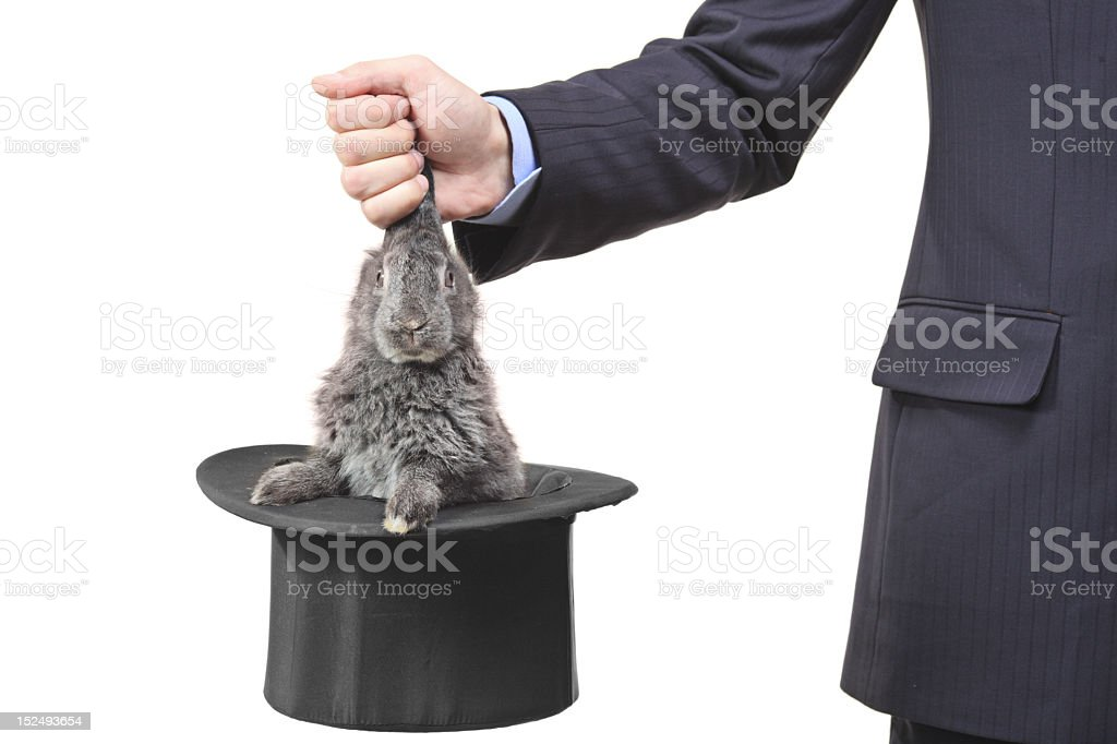 Business man pulling rabbit out of a hat by its ears stock photo