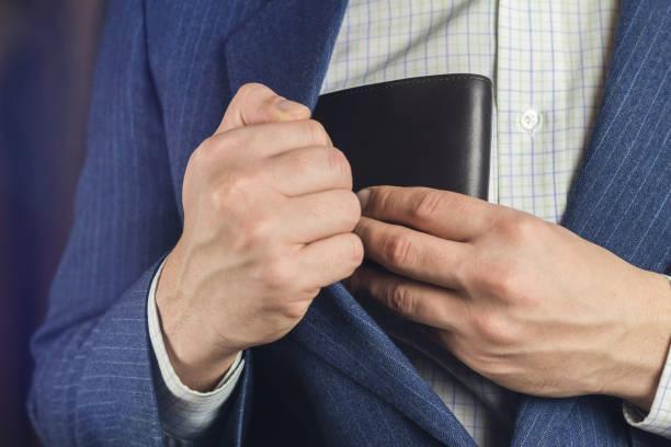 geschäftsmann zieht aus oder legt seine ledertasche in jackentasche. - leder portemonnaie herren stock-fotos und bilder