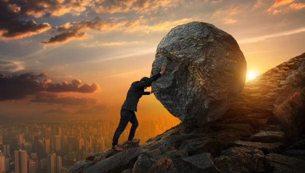 Business man pushing large stone up to hill , Business heavy tasks and problems concept. stock photo