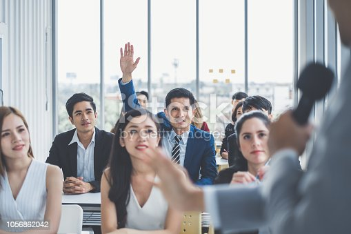 1087253494 istock photo Business man raising hand for asking speaker for question and answer concept in meeting room for seminar 1056862042