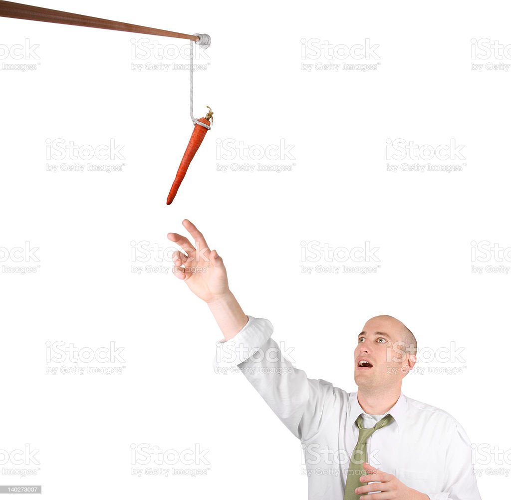 Business man reaching for carrot royalty-free stock photo