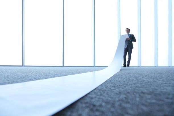 Business-Mann liest Papierrolle – Foto