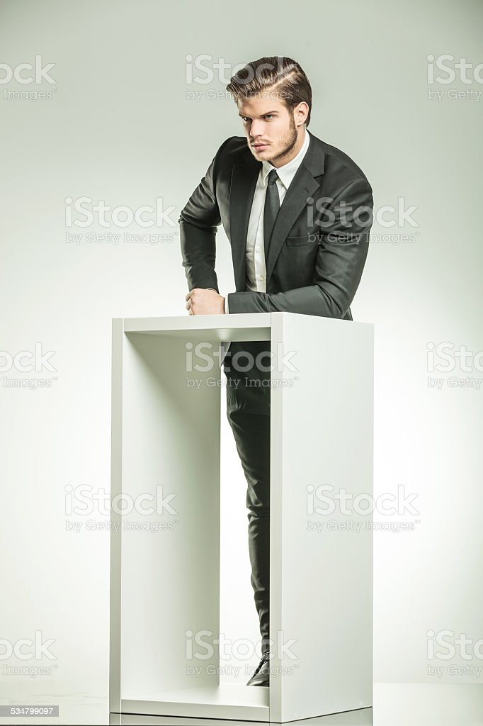 business man resting his arm on a white modern table stock photo
