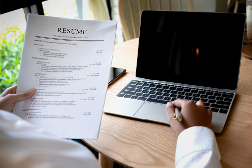 Business Man Review His Resume Application On Desk Laptop