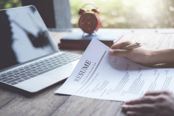 business man granska hans återuppta ansökan på skriv bord, bärbar dator, arbets sökande - new job bildbanksfoton och bilder