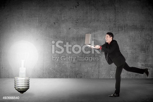 513396643 istock photo Business man run with laptop chasing light bulb 492666540