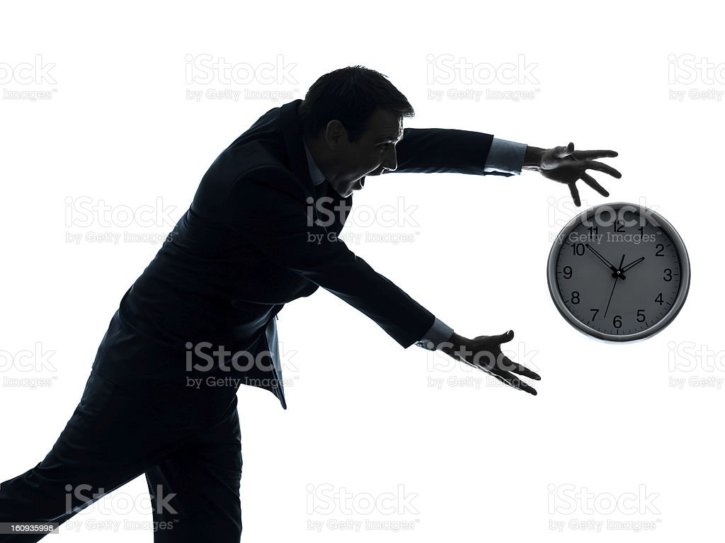 business man running after clock silhouette stock photo