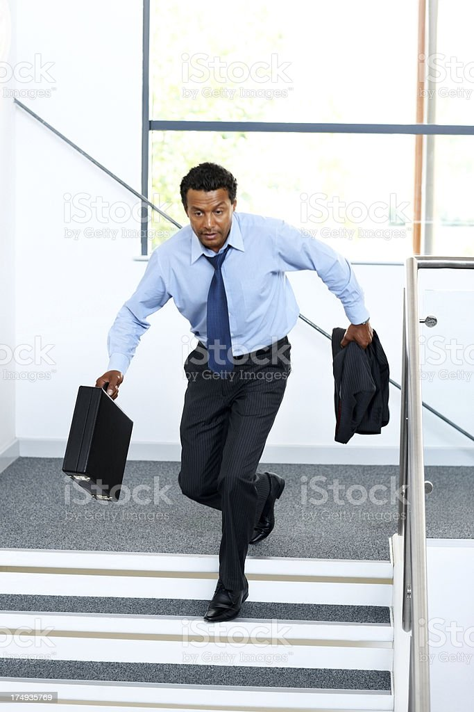 business man running down flight of stairs royalty-free stock photo