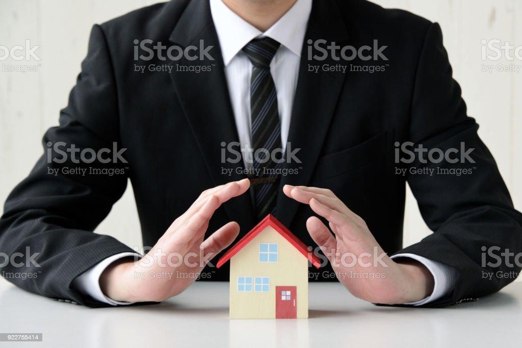 Business man saving house problems stock photo