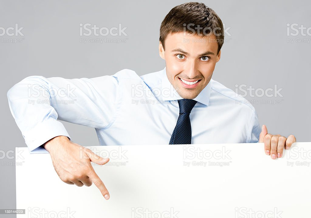 Business man showing blank signboard, over gray royalty-free stock photo