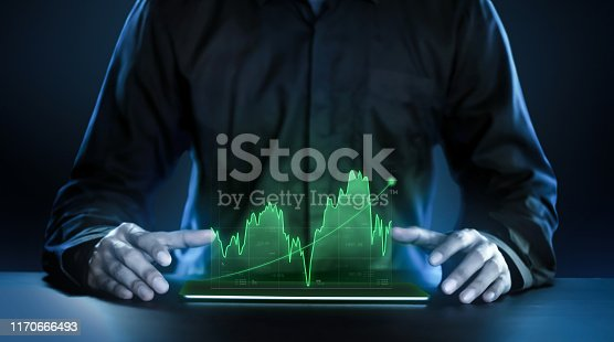 istock Business man showing profitable stock market holographic technology graphs in modern work background for the future. Company managers in concept planning and managing global marketing and investment. 1170666493