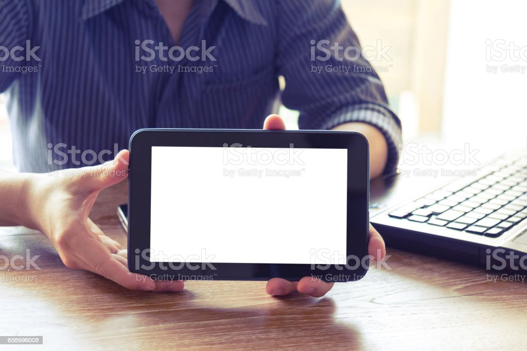 business man showing tablet computer with blank white screen on office desk – Foto