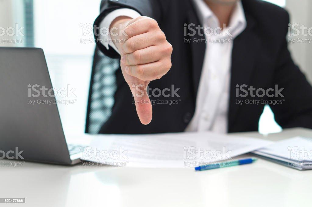 Hombre de negocios mostrando los pulgares hacia abajo en la oficina. - foto de stock