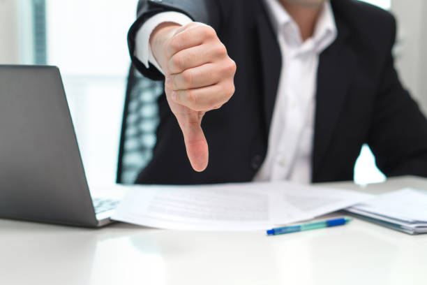 business man showing thumbs down in office. - thumbs down stock photos and pictures