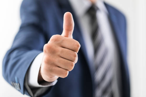Business man shows thumb up sign gesture. stock photo