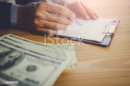 istock Business man signing a contract. Owns the business sign personally,director of the company, solicitor. Real estate agent holding house, moving home or renting property, merger and acquisition concept. 1130388353