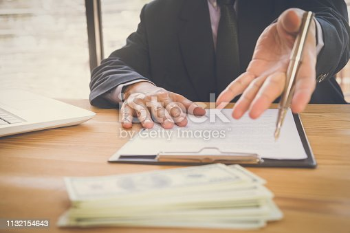 istock Business man signing a contract. Owns the business sign personally,director of the company, solicitor. Real estate agent holding house, moving home or renting property, merger and acquisition concept. 1132154643