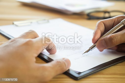 istock Business man signing a contract. Owns the business sign personally,director of the company, solicitor. Real estate agent holding house, moving home or renting property, merger and acquisition concept. 1132875720