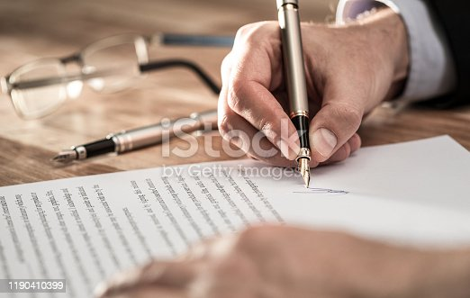 863128060 istock photo Business man signing contract, making a deal. 1190410399