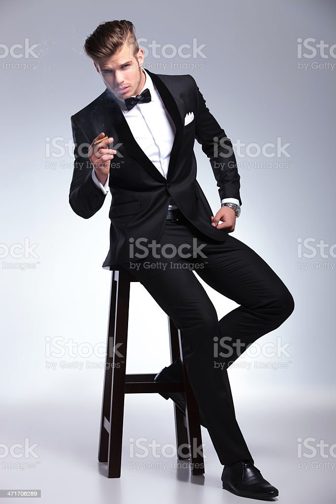 business man sits on chair and holds cigar stock photo
