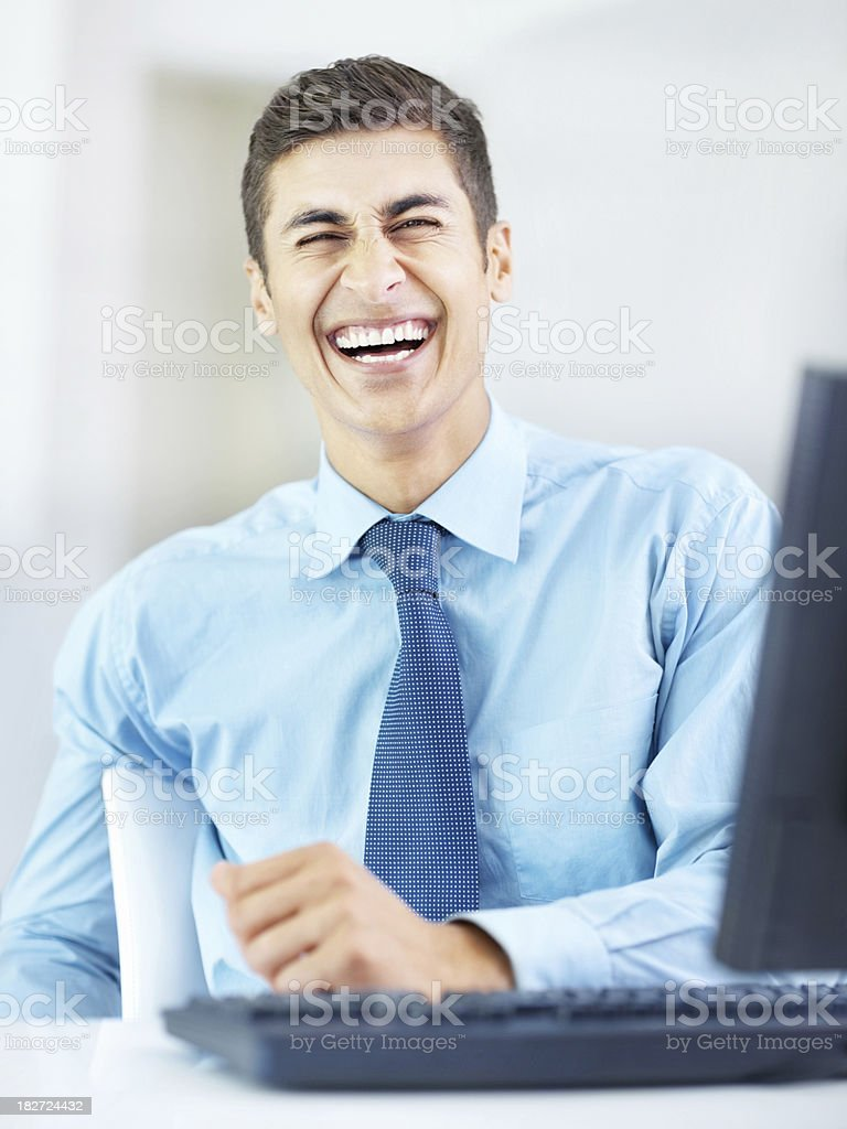 Business man sitting at the desk and laughing royalty-free stock photo