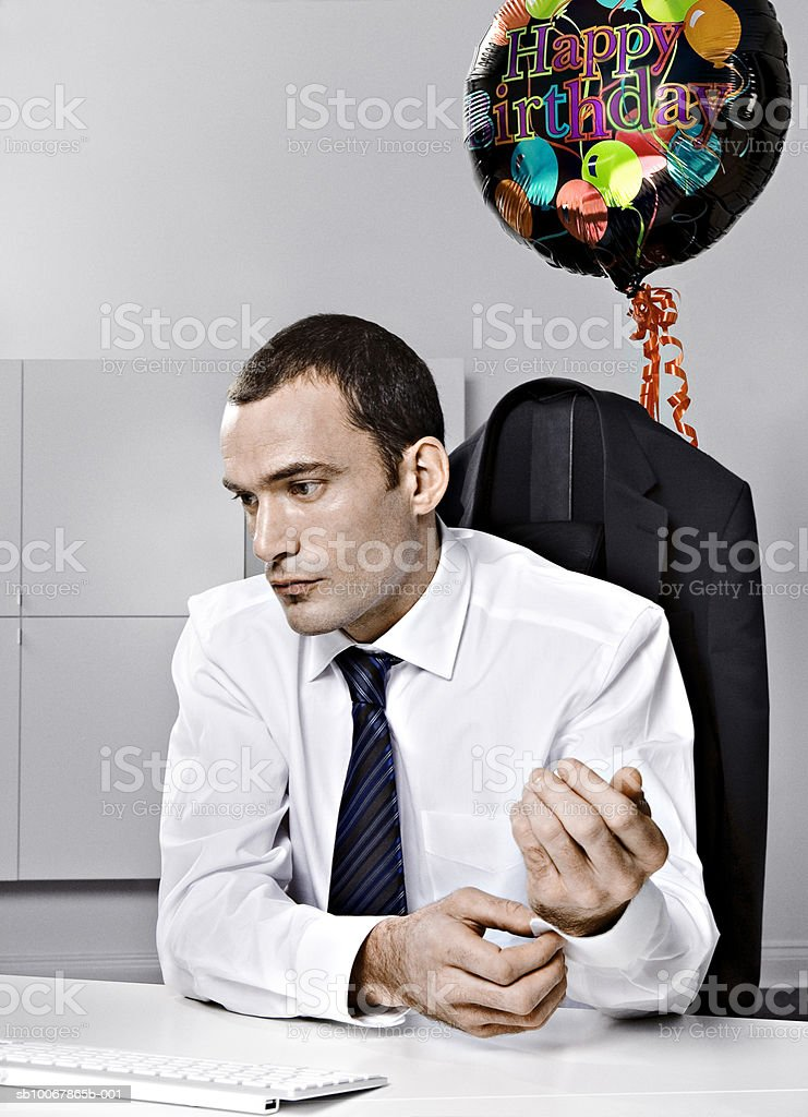 Business man sitting behind desk with baloon tied to chair foto de stock libre de derechos