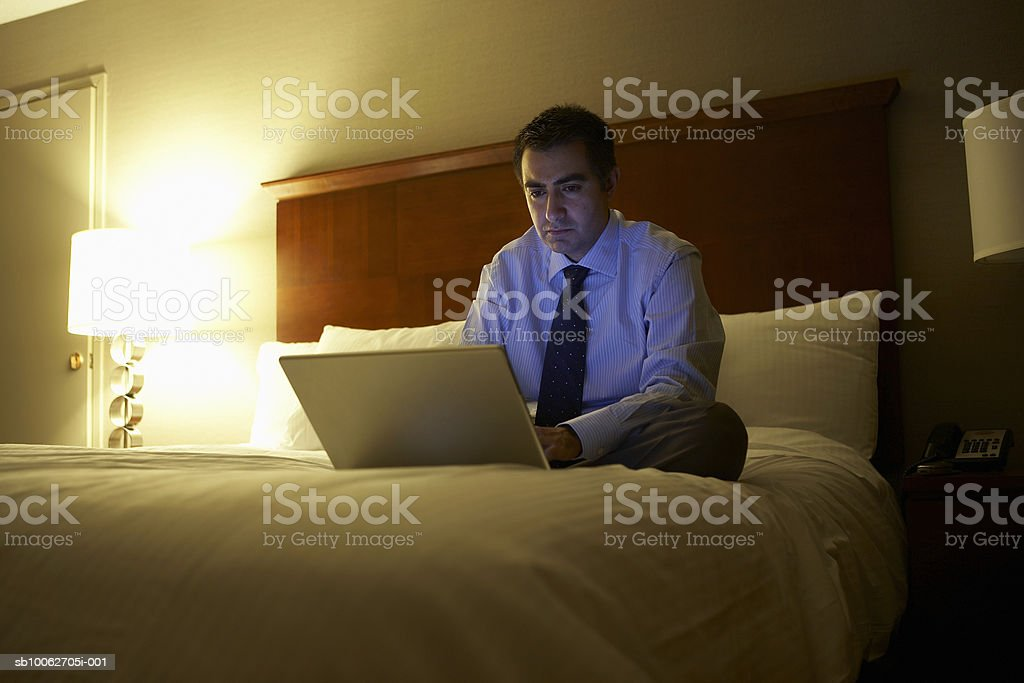 Business man sitting cross-legged on bed in hotel room working on laptop royalty-free stock photo