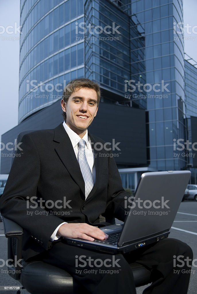 Business man sitting in front of the office building royalty-free stock photo
