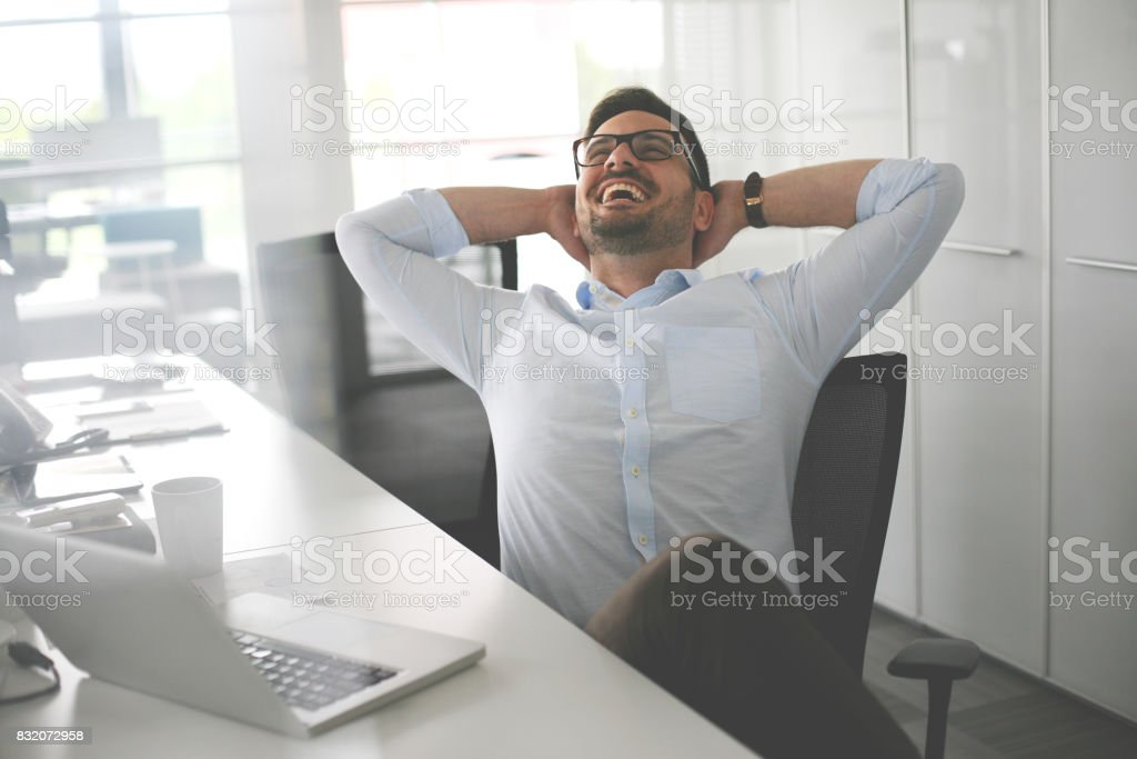 Business man sitting in office and stretched. Business man having break. stock photo
