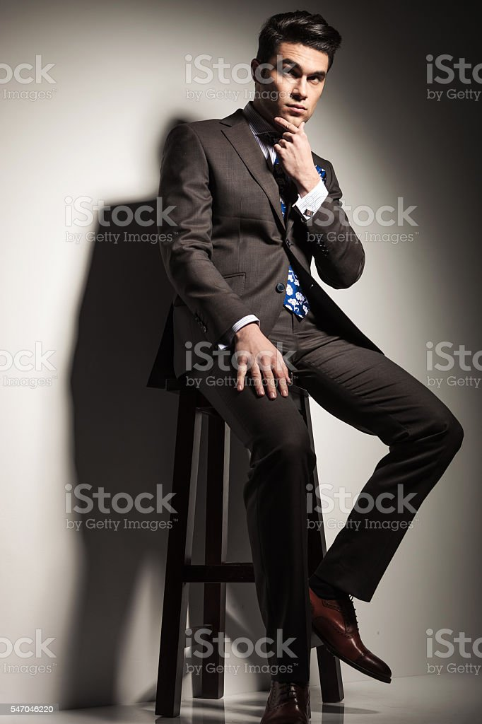 business man sitting on a stool stock photo