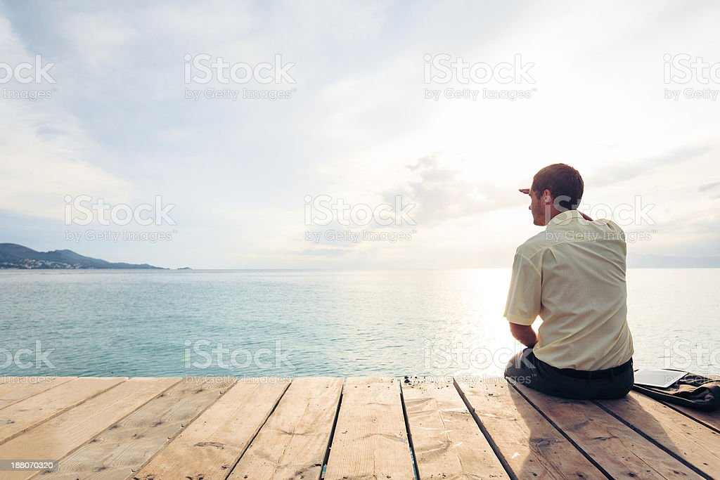 Business man sitting on pier looks out over water stock photo