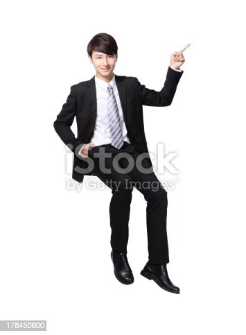 business man sitting on some thing and show copy space by finger in full length isolated on white background, asian model