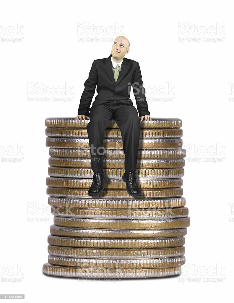 Business man sitting on stack of coins stock photo