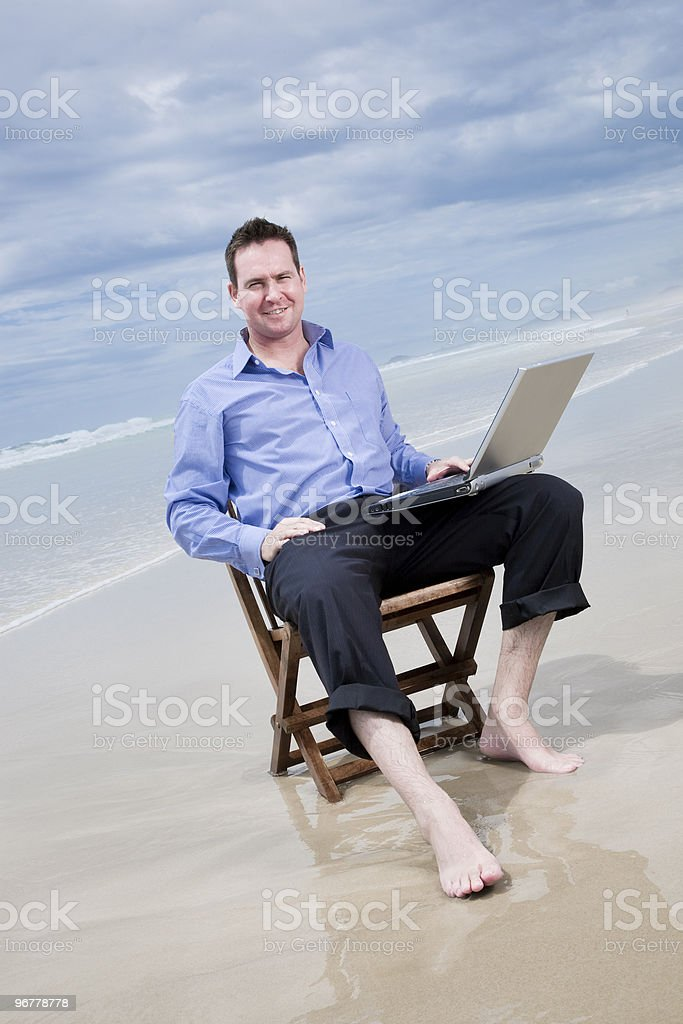 business man sitting on the beach with laptop royalty-free stock photo