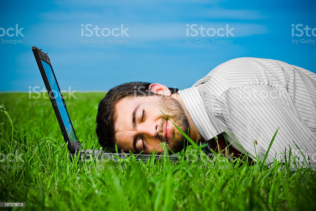 business man sleeping on laptop in the field royalty-free stock photo