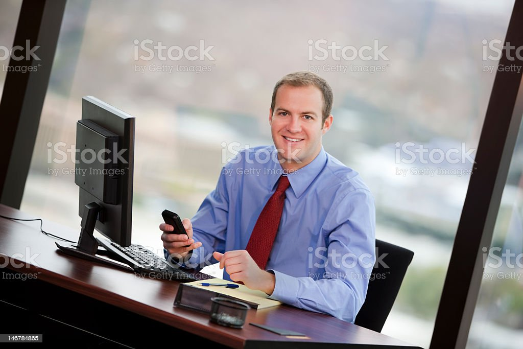 Business Man Smiling And Holding Cellphone In Office royalty-free stock photo