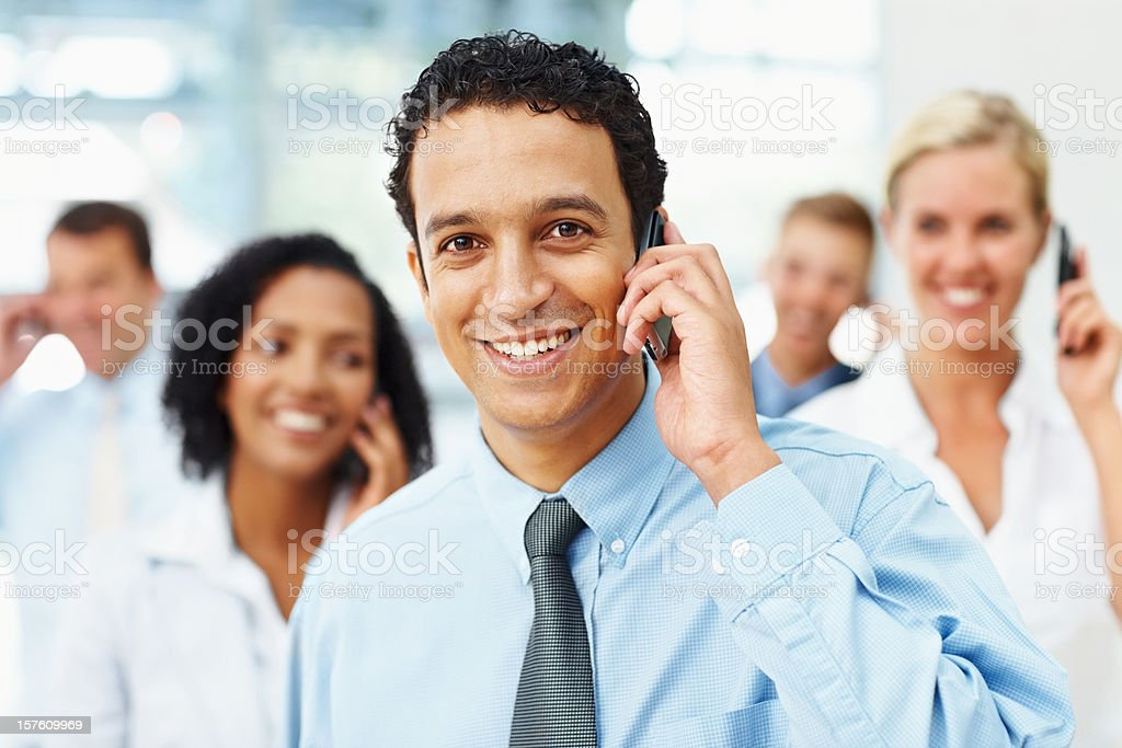Business man speaking on phone and colleagues at the back royalty-free stock photo