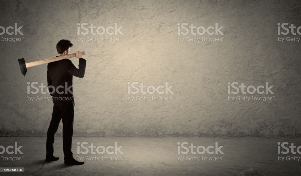 Business man standing in front of a grungy wall with a hammer stock photo