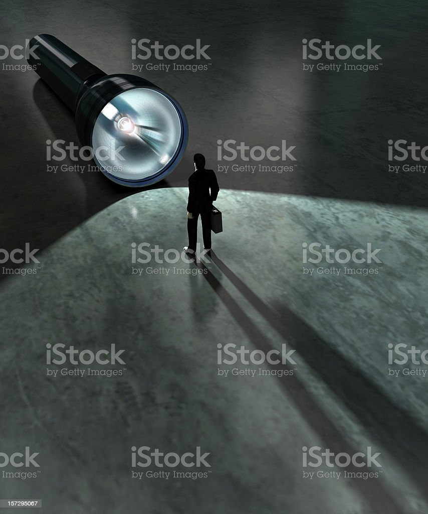 A business man standing in front of a large flashlight stock photo