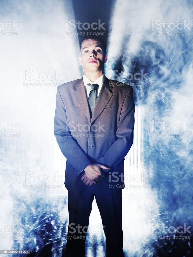 Business man standing in smoke, backlit royalty-free stock photo