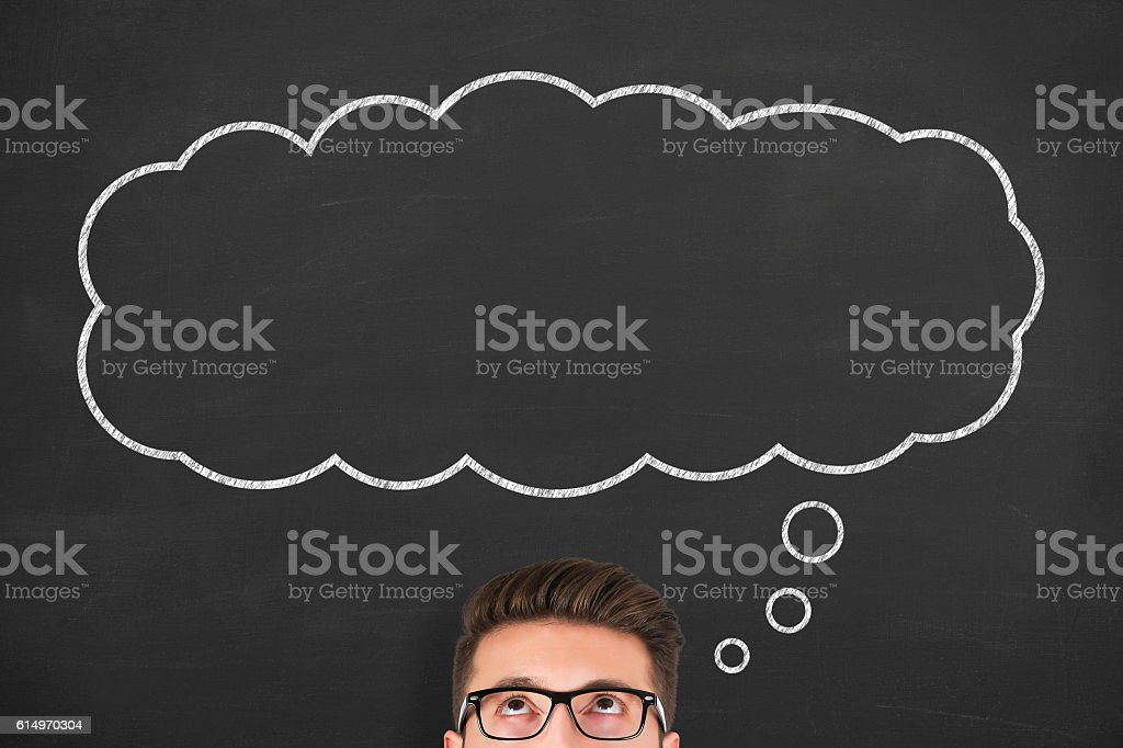 Business man standing next to thought bubble drawn on chalkboard stock photo