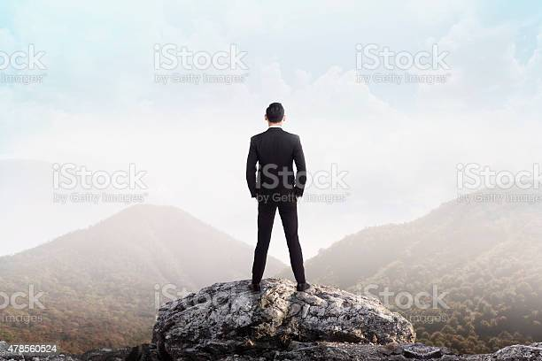 Photo of Business man standing on the top of the mountain