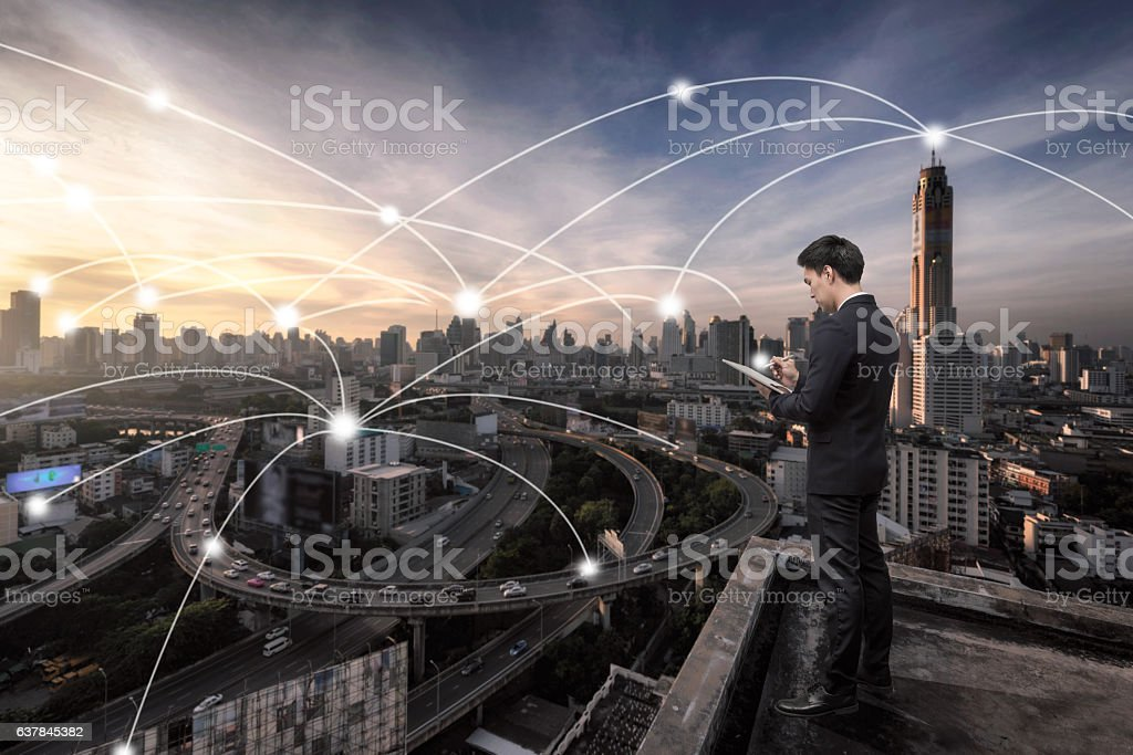 Business man standing over cityscape with connetion technology l stock photo